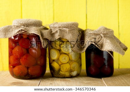 Assortment of canned vegetables in front of a wooden yellow  background  - stock photo