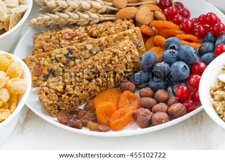 assortment of cereal muesli bars, fresh and dried fruit for breakfast, closeup, top view - stock photo