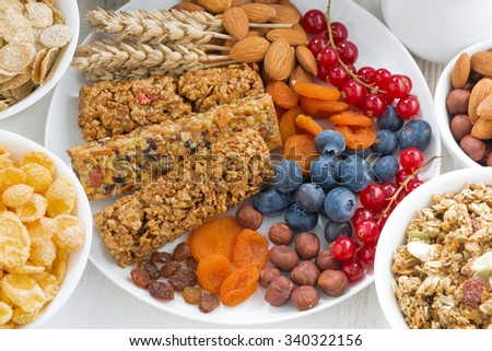 assortment of cereal muesli bars, fresh and dried fruit for breakfast, closeup, top view, horizontal - stock photo