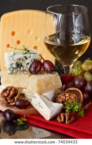 Assortment of cheese, red and green grapes and nuts.