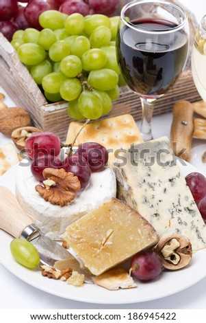 assortment of cheeses, glass of red wine, grapes and crackers, close-up, vertical