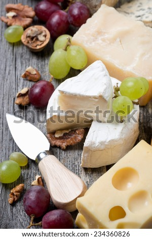 assortment of cheeses, grapes and walnuts on a wooden background, top view, vertical