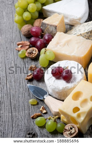 assortment of cheeses, grapes and walnuts on a wooden background, vertical