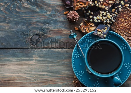 Assortment of chocolate and cup of coffee on wooden table - stock photo