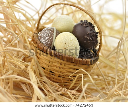 assortment of chocolate eggs in a basket, close up - stock photo