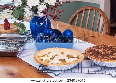 Assortment of Christmas and Thanksgiving holiday pies and a pan of brownies. Cherry pie, apple pie, walnut pumpkin pie, and deep chocolate brownies served on a wood dining room table. - stock photo