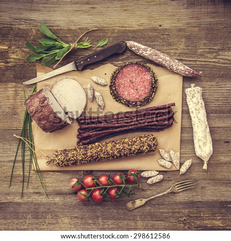 Assortment of cold meats over wooden background - stock photo