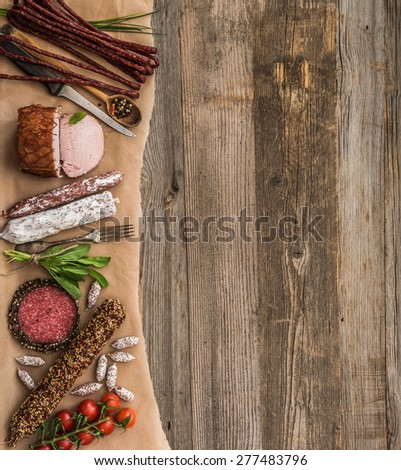 Assortment of cold meats over wooden background with space for text - stock photo