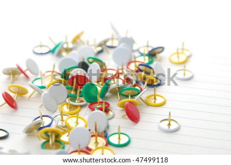 assortment of colored tacks laying on paper - stock photo
