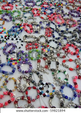 Assortment of colorful bracelets on market stand - stock photo