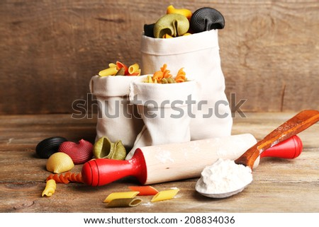 Assortment of colorful pasta in bags, rolling-pin on cutting board, on wooden background - stock photo