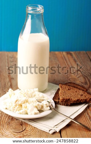 Assortment of diary products for breakfast (homemade cottage cheese; milk) with rye bread on a wooden table. Selective focus - stock photo