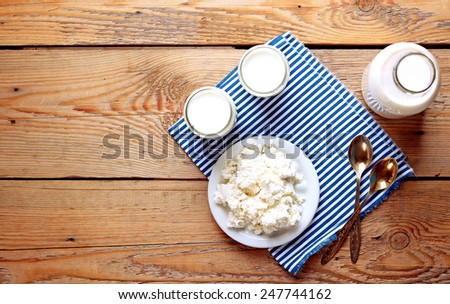 Assortment of diary products for breakfast (homemade yogurt, cottage cheese; milk) on a wooden table. Top view, selective focus, copy space background - stock photo