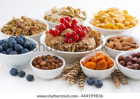 assortment of different breakfast cereal, dried fruit and berries, horizontal
