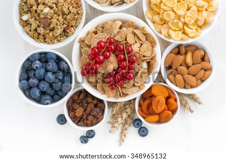 assortment of different breakfast cereal, dried fruit and fresh berries on white wooden table, top view, horizontal