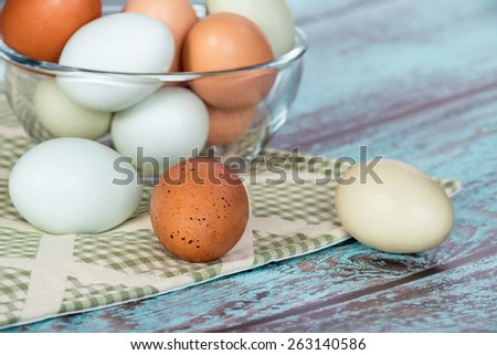 Assortment of different color, fresh chicken eggs in a glass bowl, vintage green background