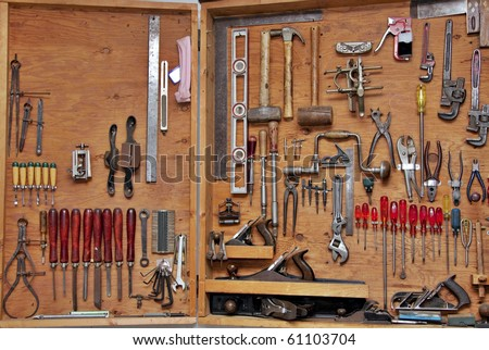 assortment of DIY do it yourself tools hanging in a wooden cupboard against a wall - stock photo