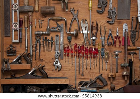assortment of do it yourself tools hanging in a wooden cupboard against a wall - stock photo