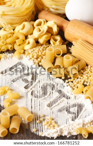 Assortment of dry pasta on a kitchen table with flour and rolling pin. - stock photo