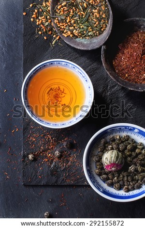 Assortment of dry tea and cup of hot tea. Green tea, black tae, green tea with rice, rooibos, dry rose buds in porcelan and old metal chinese bowls. Black textured slate background. Top view. - stock photo
