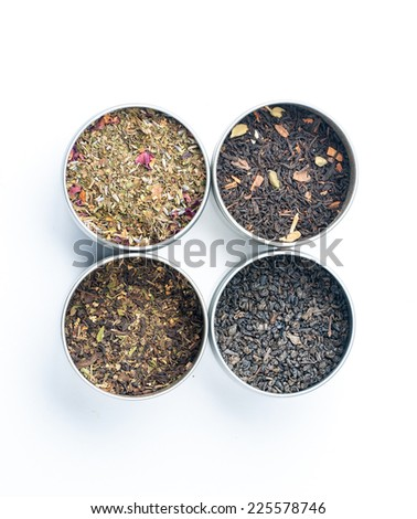 Assortment of dry tea in containers, isolated on white background - stock photo