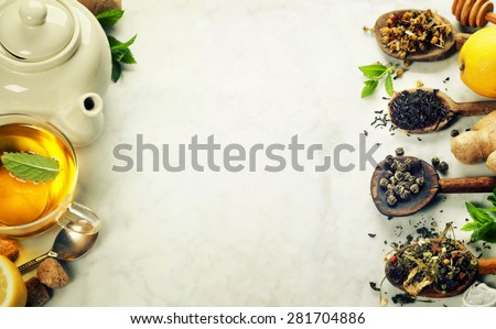 Assortment of dry tea in spoons on marble background - stock photo