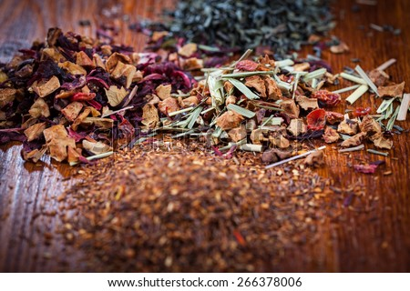 Assortment of dry tea on wooden table - stock photo