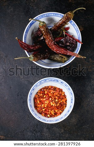Assortment of dryed whole and flakes red hot chili peppers in ceramic bowls over black background - stock photo