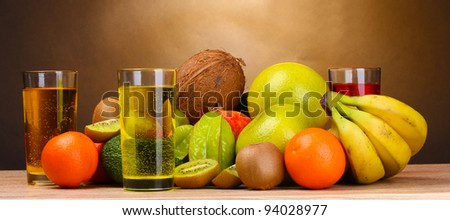 Assortment of exotic fruits and juice on wooden table on brown background - stock photo