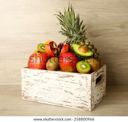 Assortment of exotic fruits in box on wooden background - stock photo