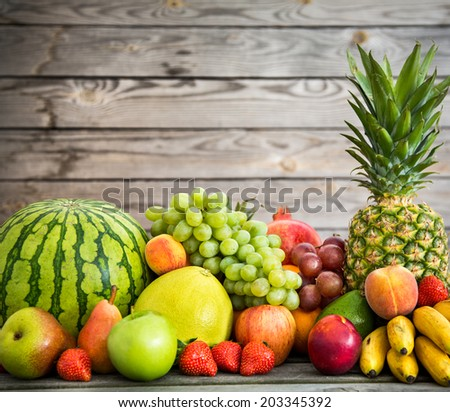 Assortment of exotic fruits on a wooden background - stock photo