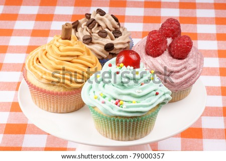Assortment of fancy cupcakes on a white porcelain cake stand. One with raspberries, one with candied cherry, one with coffee and one with carrot and cinnamon. - stock photo