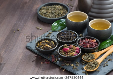 assortment of fragrant dried teas and green tea on dark wooden table, horizontal - stock photo