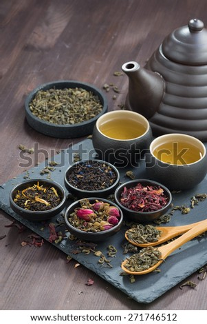 assortment of fragrant dried teas and green tea on wooden table, vertical - stock photo