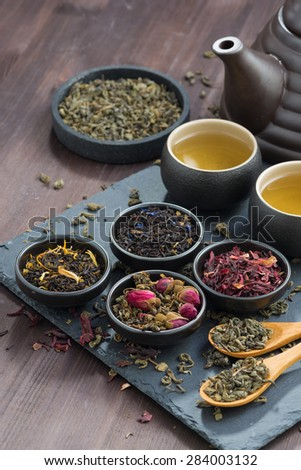assortment of fragrant dried teas and green tea, vertical, top view - stock photo