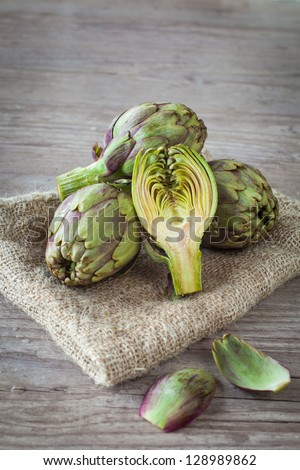 Assortment of fresh artichokes on wooden background - stock photo