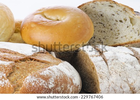 Assortment of fresh baked Artisan Breads including Whole Grain, Rye, Barley, Oatmeal and Flax seed, White Sandwich Loaf, Dinner Rolls, and a Bagel - stock photo