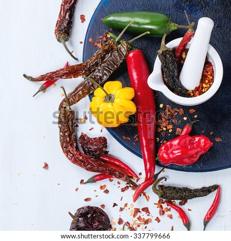 Assortment of fresh, dryed and flakes hot chili peppers with white ceramic mortar on dark blue cutting board over light blue wooden background. Top view. Square image - stock photo