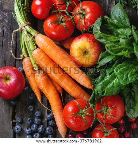 Assortment of fresh fruits, vegetables and berries carrot, spinach, tomatoes, red apples, blueberries and cranberries over old wooden table. Flat lay. Square image - stock photo