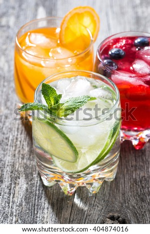 assortment of fresh iced fruit drinks on wooden background, vertical, closeup - stock photo