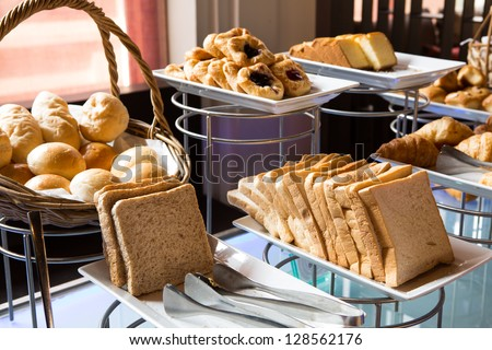 Assortment of fresh pastry on table in buffet - stock photo