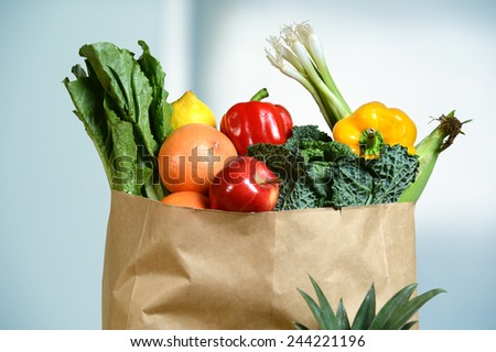 Assortment of fresh produce in grocery paper bag by window - stock photo