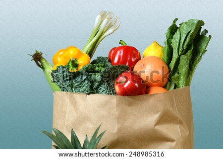 Assortment of fresh produce in grocery paper bag over gradient background - stock photo