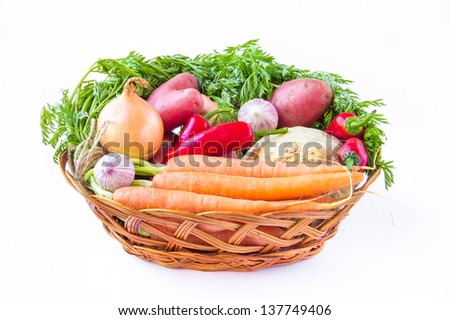Assortment of fresh young vegetables in a basket on white - stock photo