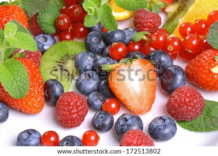 Assortment of fruits and berries on a white surface