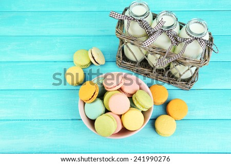 Assortment of gentle colorful macaroons in colorful bowl milk bottles on color wooden background - stock photo