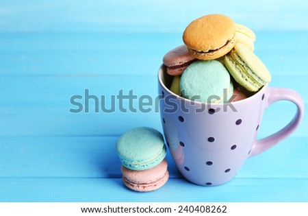 Assortment of gentle colorful macaroons in colorful mug on color wooden background - stock photo