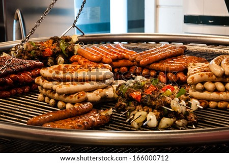 Assortment of grilled sausages and kebabs on big hanging grill at Christmas market in Paris.