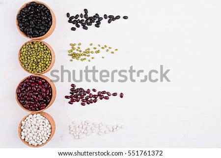 Assortment of haricot in a wooden bowls with copy space and tracks beans on white wood background. Top view, closeup. Healthy protein food.