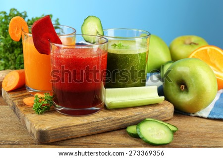 Assortment of healthy fresh juices in glass bottles on wooden table, on blue background - stock photo